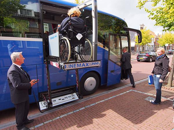 Henk Sjollema bedient de rolstoellift tijdens de eerste reis met senioren in Sneek. Rechts reisleidster Marnejaeike Bouwmeester uit Warten, touroperator bij Friesland Holland Travel.