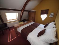 Authentieke elementen van de voormalige hooizolder hebben de Bosgra's ook in de hotelkamers intact gelaten.