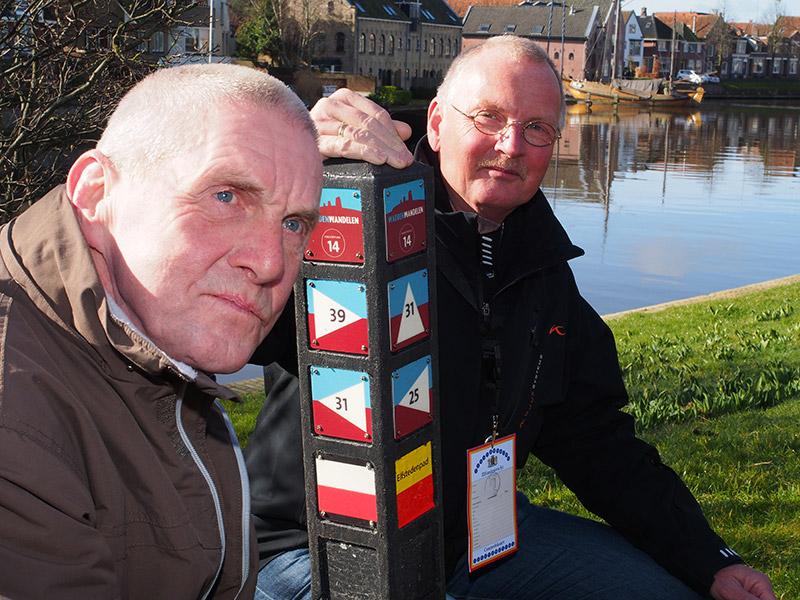 """Johan Vellinga (links) en zijn """"supporter"""" Tjisse Brookman, voorzitter Koninklijke Wandel Bond Nederland, regio Fryslân, bij knooppunt Dokkum."""