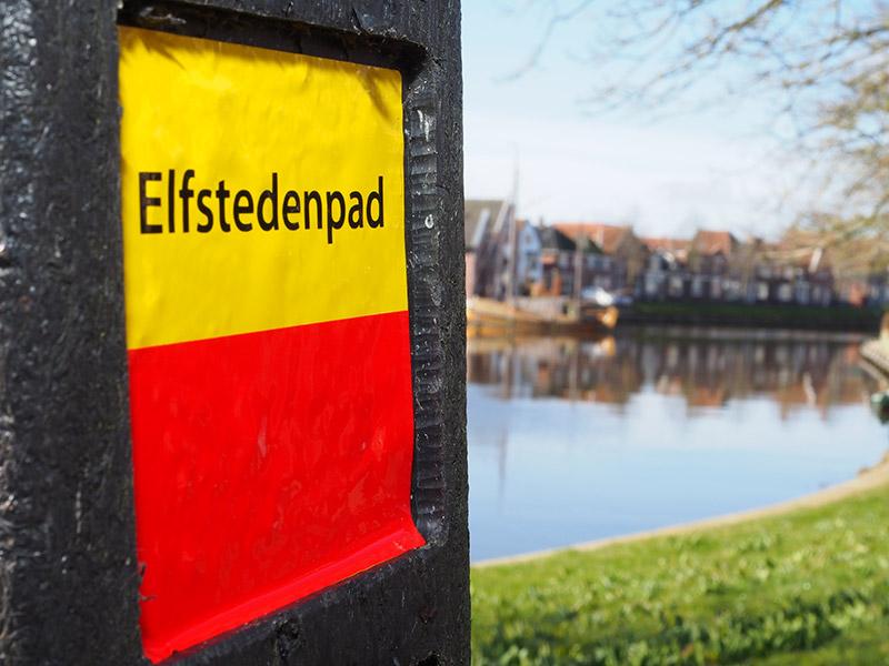 In 2017 kom je op de hele Elfstedenroute deze paaltjes met het geel-rode vignet van het Elfstedenwandelpad tegen. Aan het Dokkumer Grootdiep (Grutdjip in het Fries) nabij hotel De Posthoorn bevindt zich Elfstedenwandelpad-knooppunt 14. Dit paaltje maakt ook deel uit van de Waddenwandelroute: http://www.waddenwandelen.nl/nl/p/