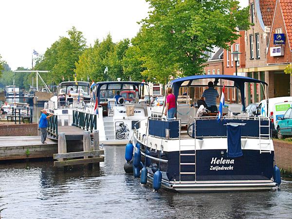 De hele Turfroute wordt in fasen uitgebaggerd tot 1,30 m, zodat toeristen ook met grotere 4- tot 12-persoons charterkruisers de leuke plaatsen en attracties van de Friese Wouden kunnen bereiken. Op de foto passeren motorjachten uit het westen van Nederland de sluizen en bruggen van Gorredijk.