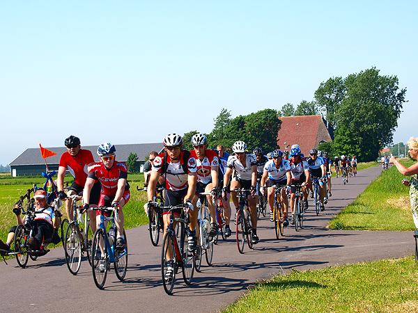 Dik 14.000 fietsers reden in colonnes en in een flink tempo op één dag de Elfstedenroute, hier op het traject Sneek-Woudsend. Veel snelle fietsers droegen een helm en dat bleek, gezien de goede afloop van enkele valpartijen, geen overbodige persoonlijke bescherming.