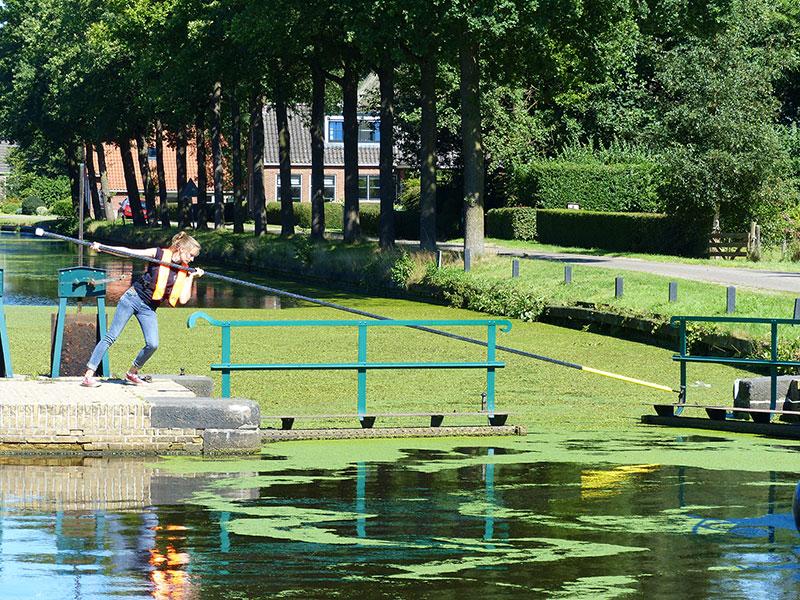 De groene sluizen van Lippenhuizen en Wijnjeterp. Sluiswachters hengelen de waterplanten uit de kolk. Fotografie: Jana Hendriks, Friesland Holland Nieuwsdienst.