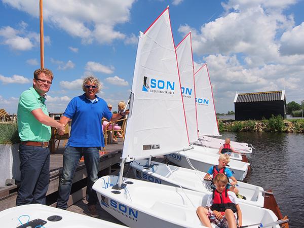 Freek Baron van SON scheepsverzekeringen (links) feliciteert Jan Feike Hoekstra van Zeilcentrum Grou met de nieuwe jeugdzeilboten.