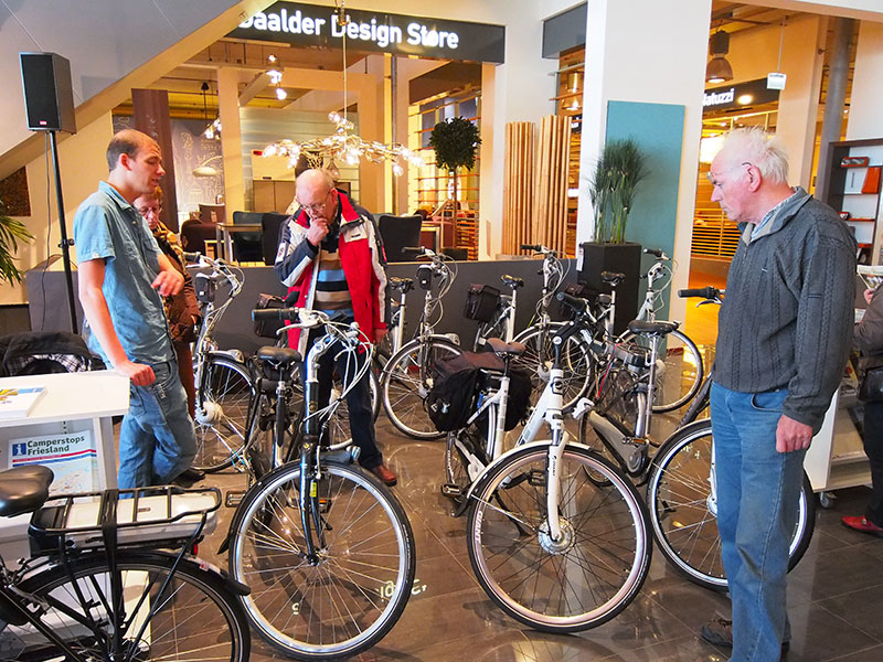 Frank Hendriks van fietsvakantiespecialist Friesland Holland (links) informeert bezoekers over Koga e-bikes. Deze exclusieve en prijzige fietsen worden ingezet bij e-bike testarrangementen van Friesland Holland Travel. Jarenlange ervaring op de Elfstedenroute (254 km) leert dat de duurste fietsen lang niet altijd technisch de betrouwbaarste zijn. Dat geldt voor meerdere merken.