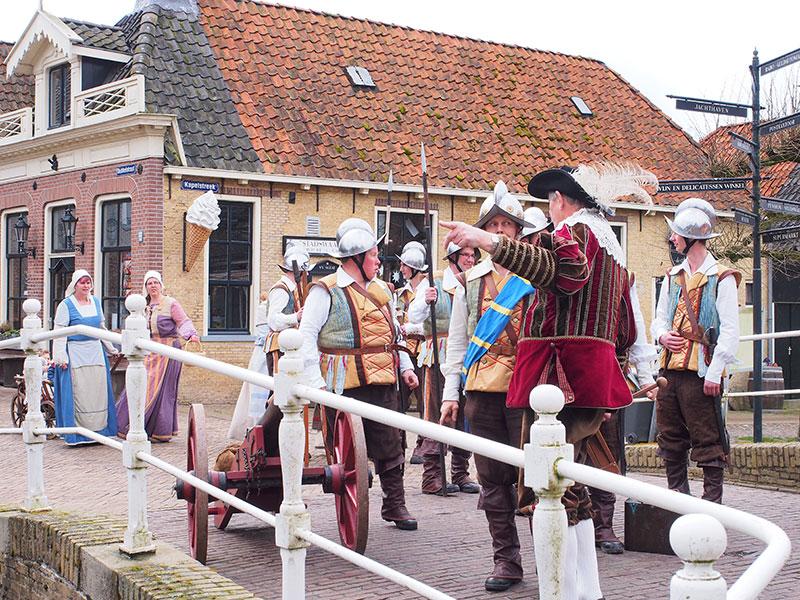 Elfstedenman Henk Kroes spreekt de genodigden toe in een afgeladen raadzaal van het oude stadhuis van Sloten. Rechts van het spreekgestoelte Bavo Galama.