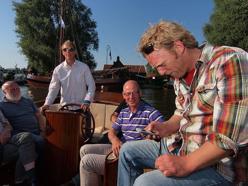 """De jacht op de coördinaten en antwoorden. Gelegenheidsgamer Durk van der Wal kan goed omgaan met de smartphone van GameEvents. """"Ik heb ook zo'n ding juh."""" Jan Riemersma (met gestreept waterpoloshirt) lacht om Durk's coole houding, terwijl Rintje zich """"de tong út 'e bek"""" stuurt om de manoeuvres uit te voeren op last van een """"commandant"""" met een GPS-toestel in een andere sloep."""