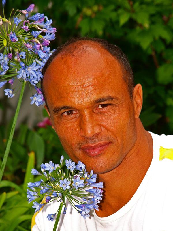 Daniël Hoek bij een Afrikaanse bloem in de tuin van Michiel en Hanneke Hoek in Oudemirdum.
