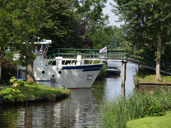 Markant Friesland Cruise. Het cruiseschip Wetterprinses passeert het Elfstedenbruggetje in Bartlehiem.