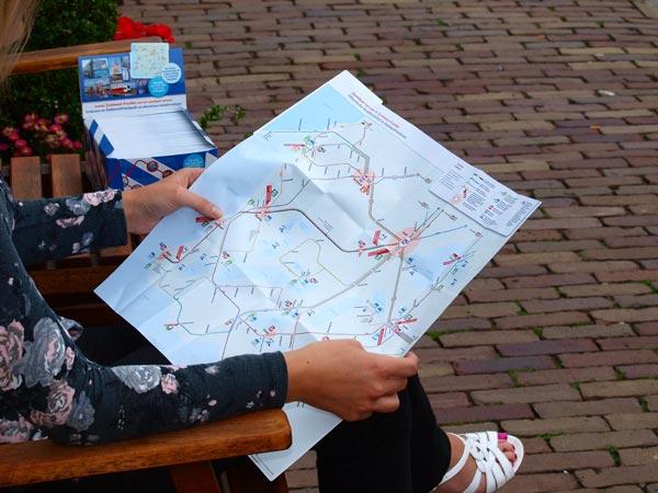 Alinde Holsappel, touroperator bij Friesland Holland, toont de nieuwe OV-toeristenkaart.