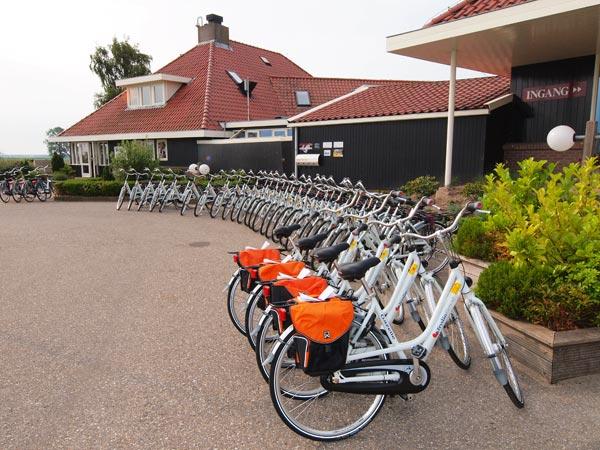De eerste serie Fryslân Fietsen voor de deur van hotel Galamadammen in Koudum. De voorste vier, met oranje fietstassen, zijn voor gasten van Friesland Holland Travel die de Elfstedentocht fietsen.