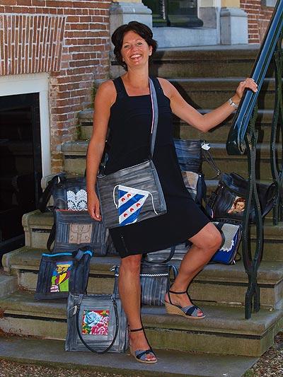 Jeannette Roeles heeft een hechte band met haar man en kinderen, maar ook met een fietsband. Hier draagt ze een geheel van oude fietsbanden gemaakte tas met een fietsvlaggetje van Friesland Holland Travel Service.