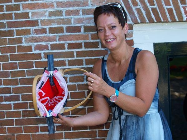 """Dit is geen les gynaecologie maar een kijkje in een afgedankte handtas met een voering van een badstoffen bardoekje van Sonnema. """"Mut kinne"""" of """"mot kunn'n"""" is het motto van kunstenares Rosemarie Koning die in het platproatende Wolvega een schoenenzaak runt."""
