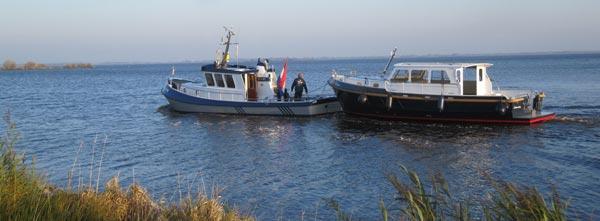 Een Rego casco wordt door Turfskip's eigen sleepboot naar Friesland gevaren om daar afgebouwd te worden.