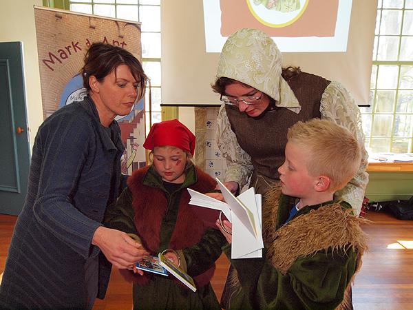 De Friese gedeputeerde voor o.a. cultuur en toerisme, Jannewietske de Vries (links) bekijkt met de in Middeleeuwse kledij gestoken Markant Friesland-coördinator Yvonne Hiemstra, en de karakters Markt en Ant, de eerste museumwaaiers.