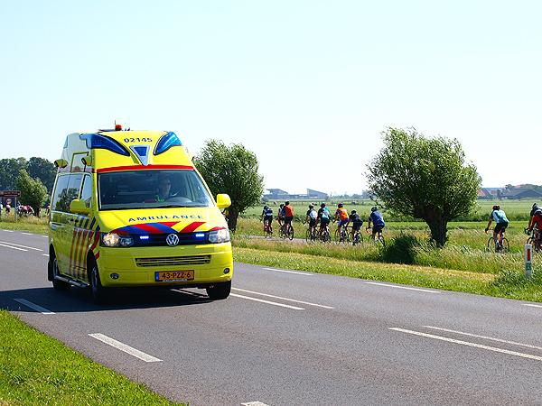 Terwijl een ambulance, met aan boord een zwaargewonde motorrijdster, met grote spoed over de N354 bij Woudsend naar het ziekenhuis van Sneek rijdt, passeren op de achtergrond deelnemers aan de fietselfstedentocht.