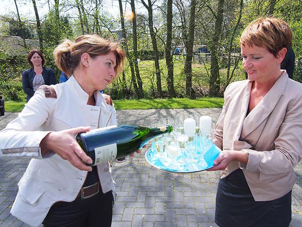 Gedeputeerde voor toerisme in Fryslân, Jannewietske de Vries, schenkt champagne in vanwege de feestelijke afronding van het Luts-project in Gaasterland. Rechts, met dienblad, Nellie de Vos, met haar man Lieuwe eigenaar van het nieuwe chaletpark De Vossenhoek in Rijs.