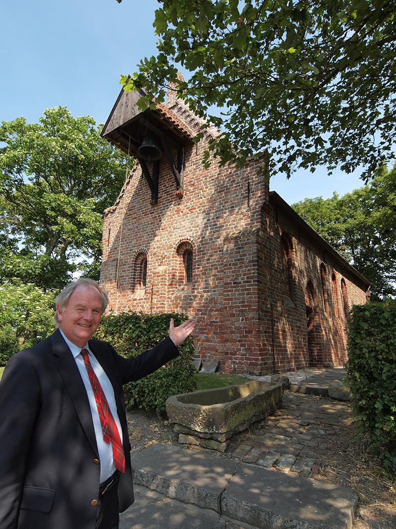 Wil van den Berg is burgemeester van de gemeente Ferwerderadiel, een regio met een bewoningsgeschiedenis van meer dan 5.000 jaar! Het kerkje van Jannum waar hij voor staat, is omstreeks 1150 gesticht. Het was vroeger een uithof van het niet meer bestaande klooster Klaarkamp (1165-1580) ten westen van Dokkum. Het Romaans aandoende Godshuisje staat op een terp, waarvan het grootste deel tot onder het maaiveld werd afgegraven. Er staan ook nog een paar gerestaureerde 19e eeuwse arbeidershuisjes. De kerk van Jannum was van 1580 tot 1938 een Hervormde kerk. Het fungeert nu als een soort museum van een bijzondere collectie sarcofagen (stenen grafkisten) uit de 11e en 12e eeuw. Buiten, aan de muur, hangt een kleine klokkenstoel. Het bouwwerk overleefde de reformatie, maar het werd wel leeggehaald. Het altaar werd in de deuropening begraven. In 1938 kwam een einde aan de functie van gebedshuis omdat de kerkgemeenschap nog maar één belijdend lid telde.