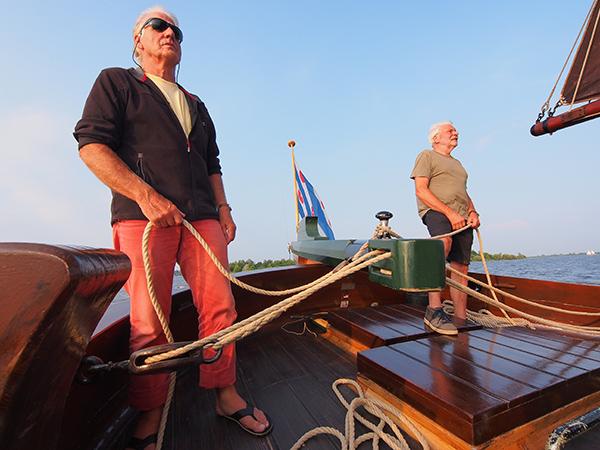 Vrijwillig schipper Sybren van der Meer, met zonnebril, stuurt de palingaak met toeristen over de Hegemer Mar terwijl hij verhaalt over het rijke palingverleden van Heeg, het Volendam van Friesland.