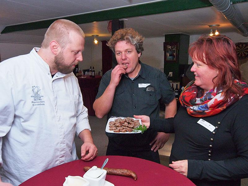 """Frieslands meest markante kok, Willem Schaafsma (links), de patron cuisinier en eigenaar van streekproductenrestaurant Eindeloos in Leeuwarden, proeft hier op het veenweidebedrijf van Steven en Klaziena van der Zee (midden en rechts) in Rohel van Friese """"drûge woarst"""" met 100% kalfsvlees. Daarin zitten kruiden die gebruikt zijn voor het maken van Weduwe Joustra Beerenburg. Schaafsma, topkok in vermaarde restaurants en boerenzoon, betrekt bijna alle ingrediënten voor zijn gerechten rechtstreeks van boeren, vissers en tuinders. Hij bezoekt ze regelmatig om een selectie te maken uit wat beschikbaar is voor verwerking."""