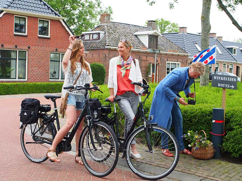 Links Ytsia Deelstra uit Blije op de lichte, elegante en hypermoderne ALBA Ciclone E-bike Sportive Edition en rechts Dorian Hofker uit Reitsum op de ALBA Ciclone E-bike Elfsteden Edition. Beide elektrische fietsen, net op de markt en eigendom van Rent a Topbike van Friesland Holland, zijn uitgerust met de beste componenten van Shimano. Ook de stille middenmotor is van Shimano! Kleding: Sake Store www.sakestore.nl Visagie: Petra Cnossen uit Oudwoude. Fotografie: Friesland Holland Nieuwsdienst. Deelnemer Nynke Runia van ambachtelijke kantoendrukkerij Kleine Lijn (www.kleine-lijn.nl) buigt zich over de bloemen van de fleurige Friese route.
