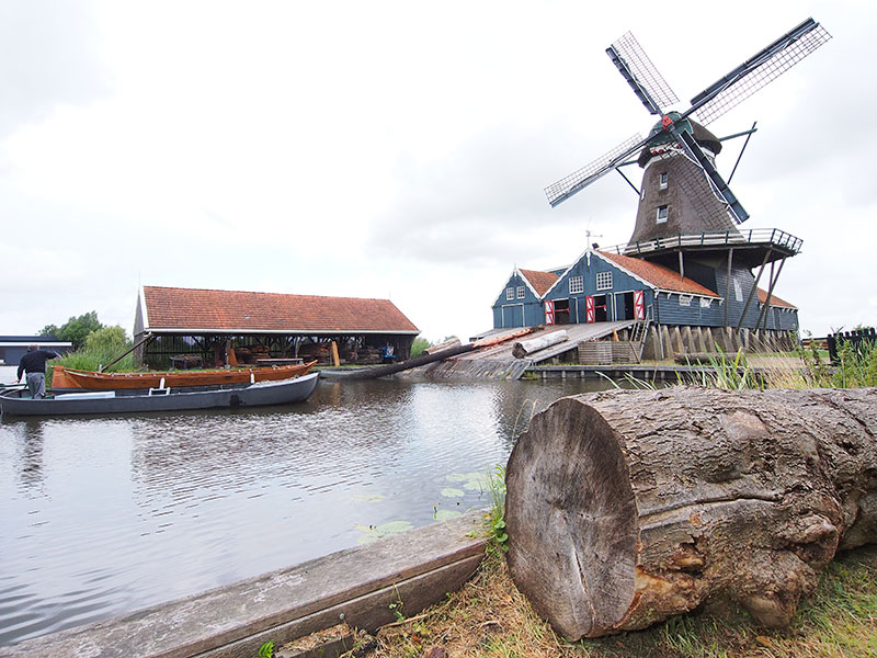 Houtzaagmolen De Rat aan het Sneekerpad in IJlst. Oorspronkelijk stond de houtzaagmolen in de omgeving van Zaandam waar hij voor 1683 als balkenzager werd gebouwd. In 1829 kocht houthandelaar Ringnalda, ook burgemeester van de stad IJlst, de zwaar verwaarloosde molen en verplaatste deze naar IJlst.  Links een houten bok, een praam. Dit scheepstype werd 300 jaar lang gebruikt voor het vervoer van hout naar aan het water gelegen Friese timmerbedrijven die boerderijen en huizen bouwden, maar ook naar houthandelaren. IJlst telde ooit acht scheepstimmerwerven en een paar grote houthandels.