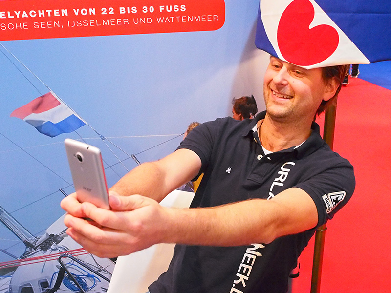 Een selfie onder een Friese lampenkap, Jappie van der Pol trekt met zijn gekkigheden meer publiek dan de buurvrouw, TUI, de grootste touroperator van Europa, die haar stand heeft gevuld met strak kijkende, keurig geklede pinguïns van Duitse reisbureaus.