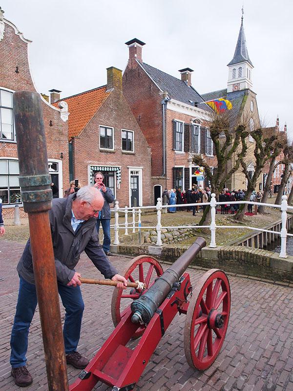 """""""It giet oan"""". Henk Kroes, de oud-voorzitter van de Koninklijke Vereniging De Friesche Elf Steden, loste het kanonschot ter gelegenheid van de onthulling van 'Pietsje en Evert van Hemert's expositie in het stadhuis op de achtergrond."""