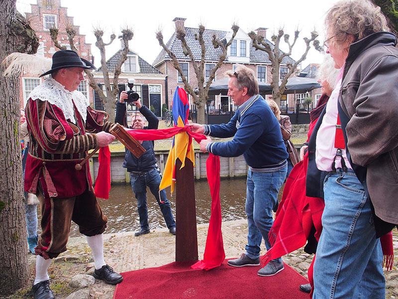 Pietsje wordt ontdaan van de stadsvlag van Sloten door Pieter Haringsma en Bavo Galama onder toeziend oog van kunstenaar Evert van Hemert (geheel rechts).