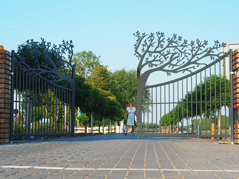 Janny Reitsema bij het indrukwekkende hek dat automatisch opengaat als je dichtbij komt.
