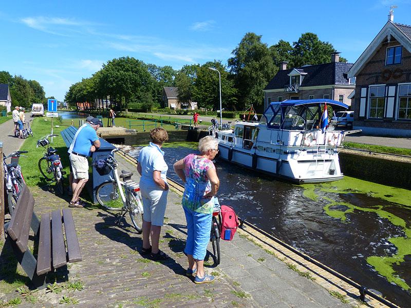 Fietsers kijken graag naar het schutten van boten die de Turfroute bevaren, zoals hier in Wijnjeterpverlaat in de gemeente Opsterland.