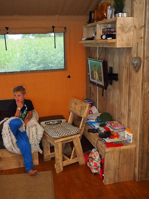 Traditioneel kamperen gaat achteruit. Helemaal hot is de glamptent, zoals deze op camping 'De Stjelp' van Aline de Jong in Oudega-Smallingerland aan de rand van Nationaal Park De Alde Feanen tussen Leeuwarden en Drachten. Glamping is vakantievieren in een vaste tent met de luxe van een vakantiewoning. De familie Smeets uit Venlo (op de foto met Aline de Jong) boekte deze zomer een safaritent van 12 bij 5 meter bij De Stjelp vanwege de ligging in de Friese Wouden. Daar kun je volgens Marco, uitvoerder bij bouwonderneming Hurks, en onderwijzeres Loes Overbeek-Smeets veilig fietsen met de kinderen Luuk, Niek en Janna, dit in tegenstelling tot bijvoorbeeld in Frankrijk. Daar is bovendien de bewegwijzering niet zo goed als in Friesland met knooppuntenbordjes. Aline de Jong kreegt de eerste 7-persoons tent op 16 april 2016 van de Emmeloorder firma Luxetenten.com die wereldwijd actief is. Foto's: ©Albert Hendriks Friesland Holland Nieuwsdienst.